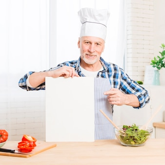 Senior male in kitchen holding paper mock-up
