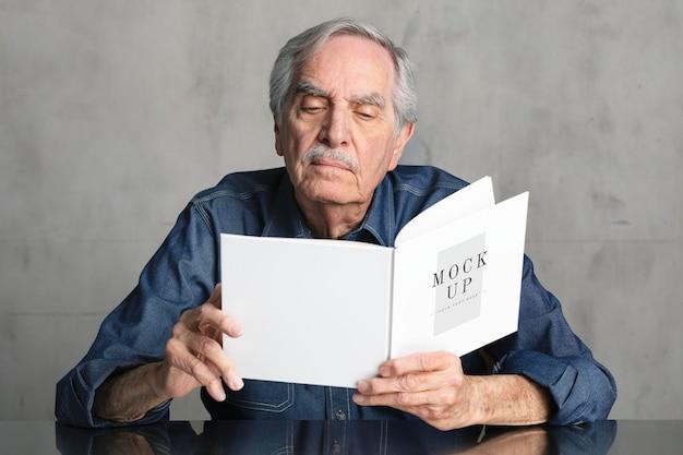 Старший мужчина читает макет книги