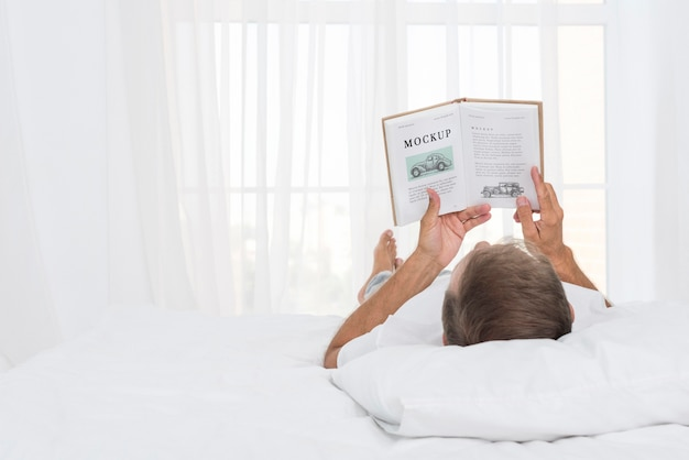 ベッドで読書をしている年配の男性
