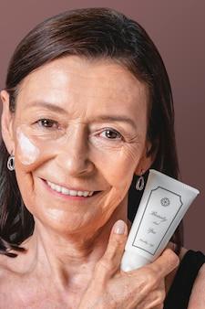 白い顔のクリーム色のチューブのモックアップを保持している年配の女性
