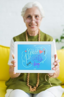 Старший женщина, держащая планшетный макет
