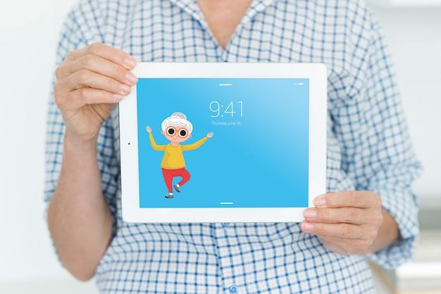 Senior woman holding tablet mockup
