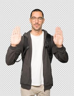 手のひらで止まるジェスチャーをする真面目な学生
