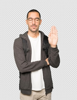 Serious student making a gesture of stop with his palm