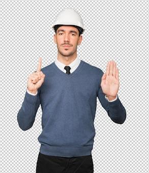 彼の手で禁止のジェスチャーをする真面目な若い建築家