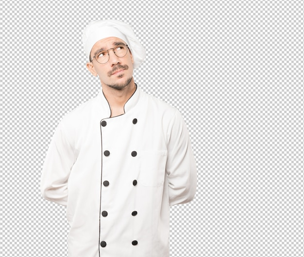 Serious young chef looking against background