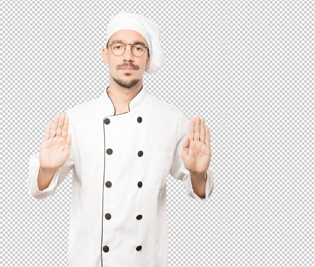 Serious young chef making a gesture of stop with his palm