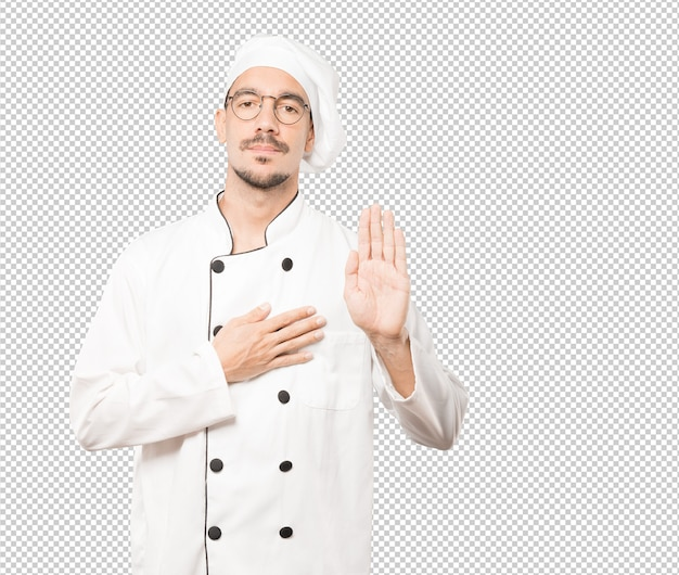 Serious young chef with a gesture of oath