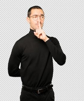 그의 손가락으로 몸짓 침묵을 요구하는 심각한 젊은 남자