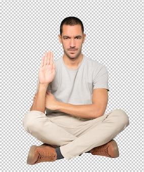 手のひらで止まるジェスチャーをする真面目な青年