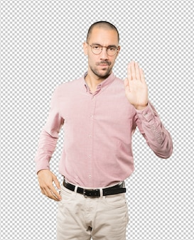 Serious young man making a gesture of stop with his palm