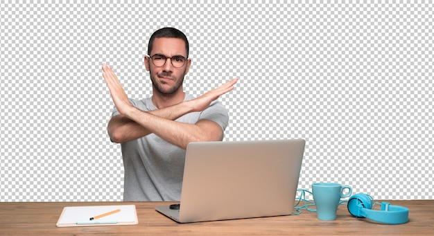 Serious young man sitting at his desk and doing a gesture of not cross
