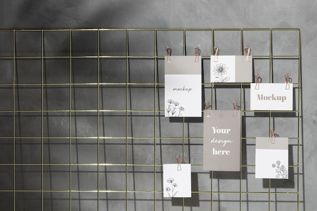 Set of cards hanging on grid memo board with clips