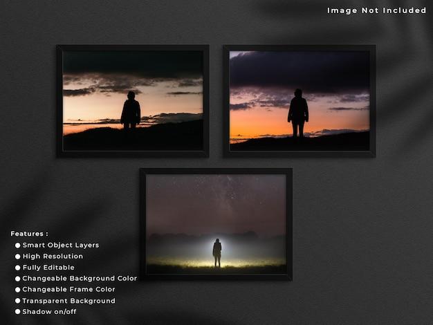 그림자가 있는 벽 배경에 매달려 있는 검은색 가로 사진 프레임 모형 세트.