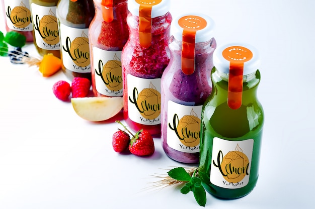 Set with color smothies in glass bottles with copy space on white