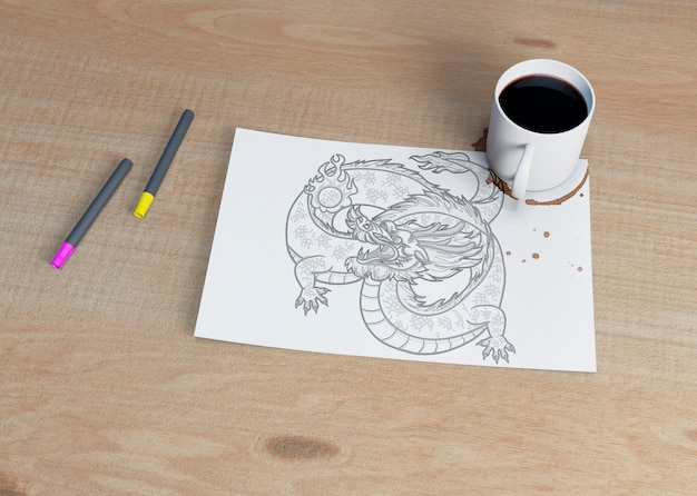 Sheet with sketch and cup of coffee beside
