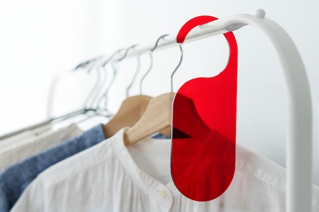 スタジオで赤いタグのモックアップが付いている衣類ラックのシャツ