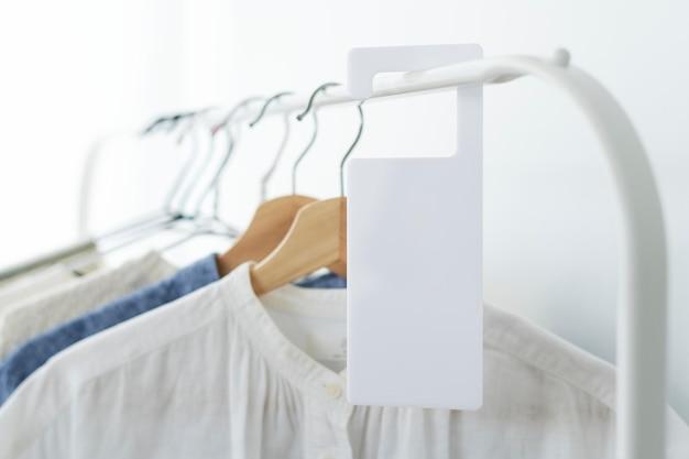 Рубашки на вешалке для одежды с макетом бирки в студии