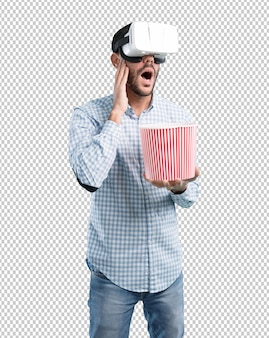 Shocked young man using a virtual reality glasses with popcorn