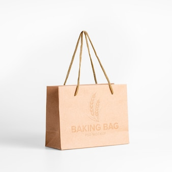 Shopping paper bag mockup with text and logo embossed on craft surface