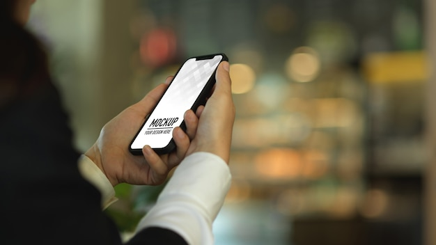 Side view of businesswoman using smartphone mockup