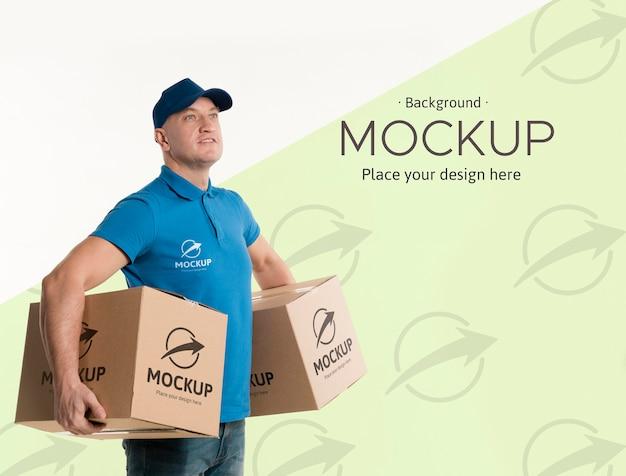 Вид сбоку доставщик, держащий коробки на его бедрах