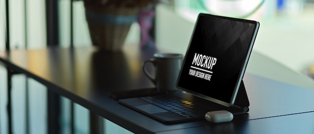 Side view of digital tablet mockup with keyboard on desk