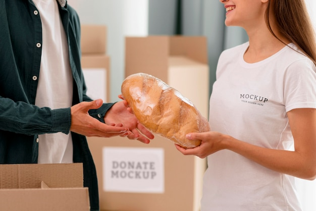 Side view of female volunteer handing out bread to man