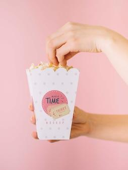 Vista laterale delle mani che mangiano popcorn