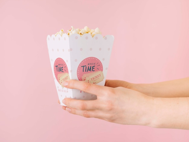 Side view of hands holding popcorn cup