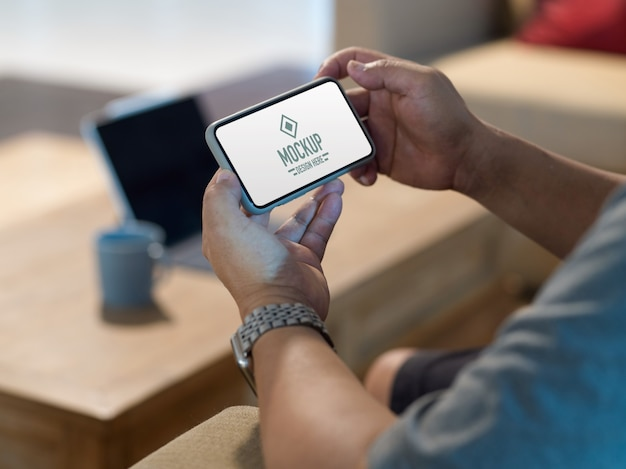 Side view of male hands holding mock up horizontal smartphone while relaxing in living room