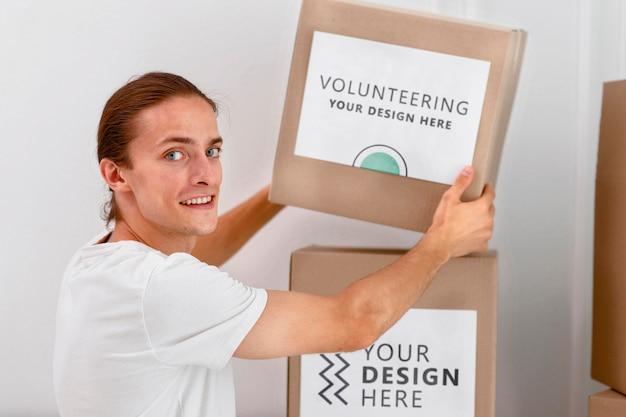 Vista laterale del volontario maschio che maneggia scatole con donazioni