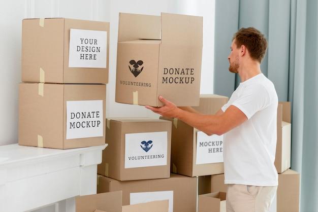 Vista laterale del volontario maschio con scatole di donazione