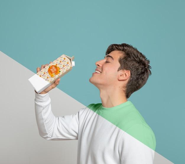 Vista laterale dell'uomo che beve dal cartone del succo