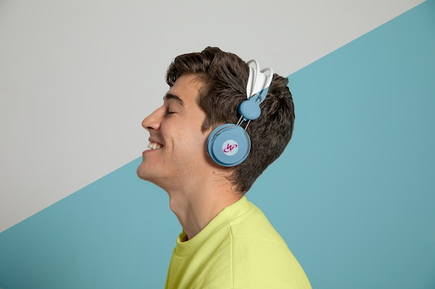 Side view of man enjoying music on headphones
