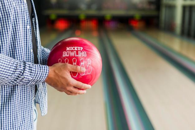 Vista laterale dell'uomo che tiene palla da bowling