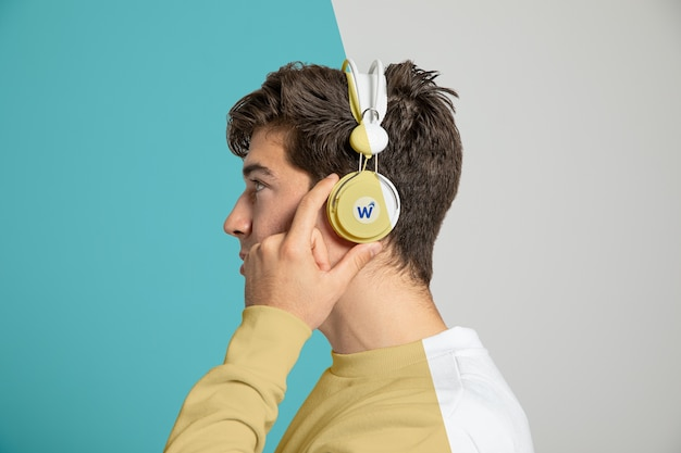 Side view of man listening to music on headphones