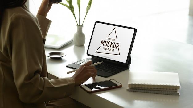 Вид сбоку на женщину-предпринимателя, работающую с макетом цифрового планшета
