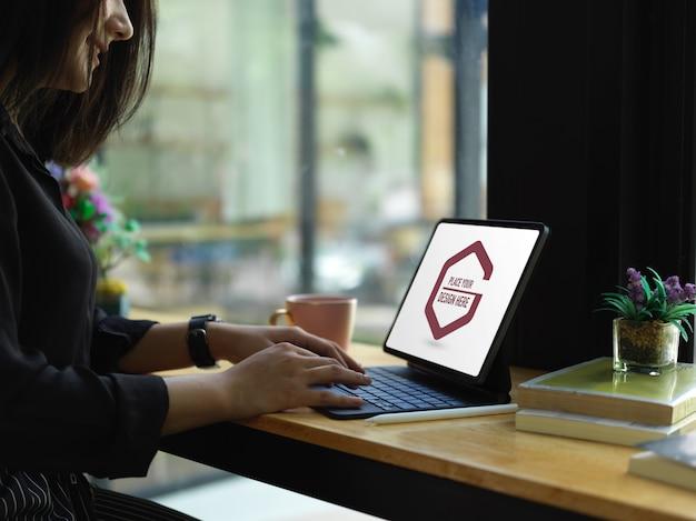 디지털 태블릿 모형으로 작업하는 여성 프리랜서의 측면보기