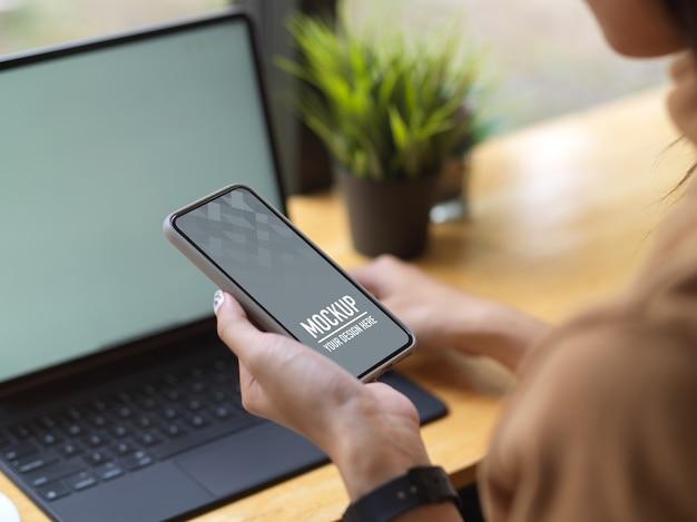 Вид сбоку женщины, держащей макет смартфона