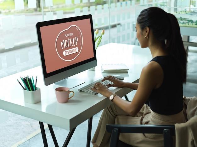 モックアップコンピューターに取り組んでいる女性会社員の側面図