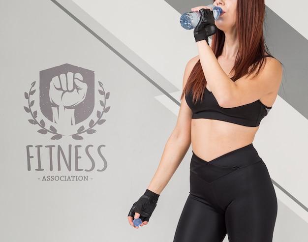 ボトルの水を飲むフィットネス女性の側面図