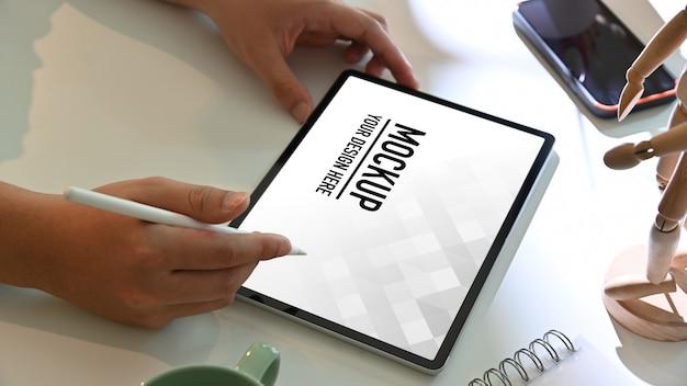 흰색 작업대에 디지털 태블릿 모형을 사용하여 남성 손의 측면보기