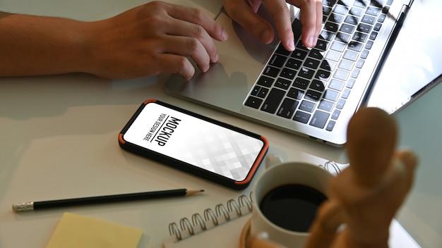 스마트 폰으로 흰색 테이블에 노트북 키보드에 입력하는 남성 손의 측면보기