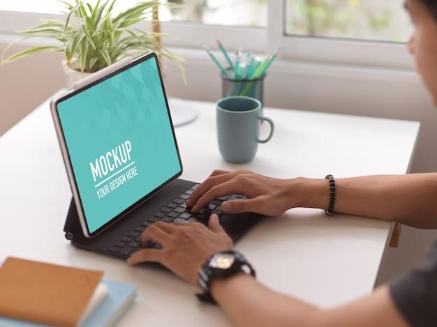 デジタルタブレットのモックアップで男性のタイピングの側面図