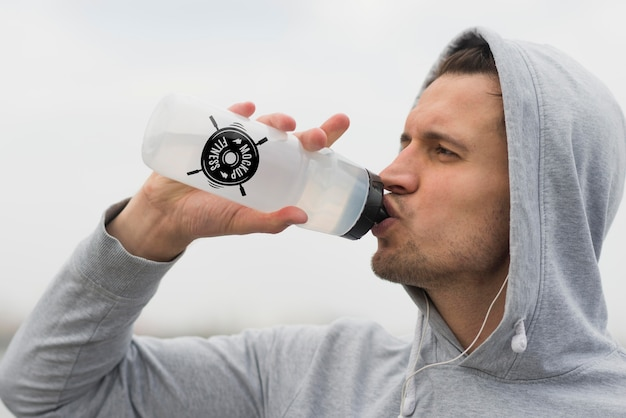 Вид сбоку человека, пьющего воду во время тренировки