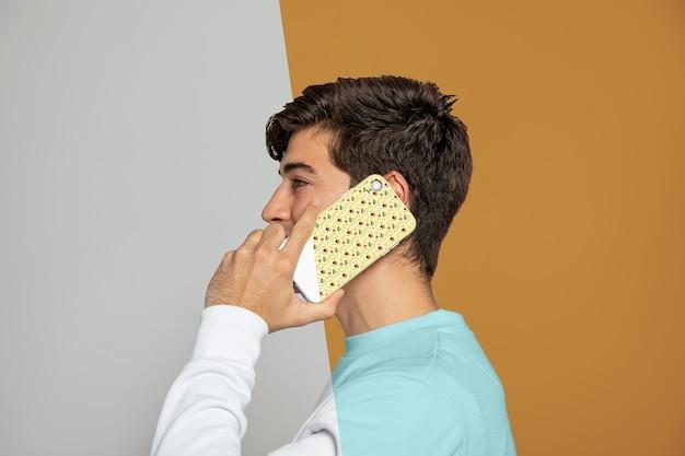 スマートフォンで話している男性の側面図