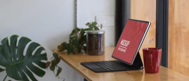 모형 태블릿 및 커피 머그가있는 휴대용 작업 공간의 측면보기