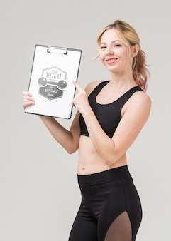 Side view of smiley fitness woman holding notepad
