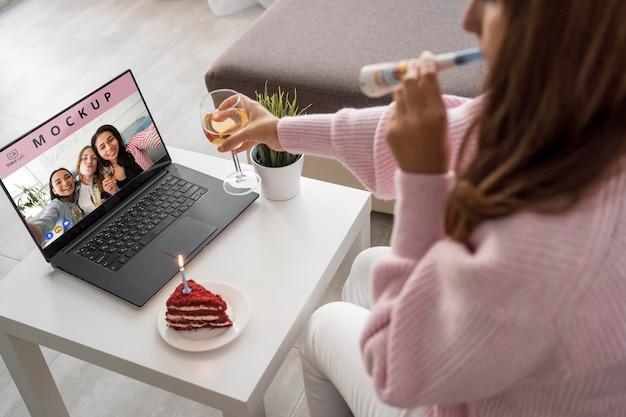 Vista laterale della donna che celebra a casa con gli amici su laptop e drink